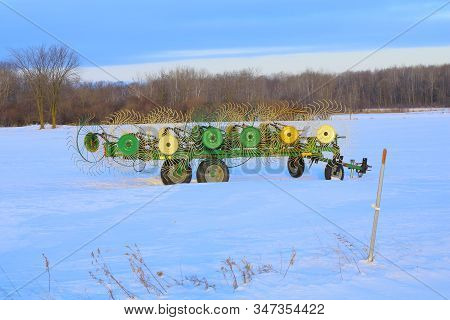 Clear Lake, Wi / Usa  - January 12 / 2020: Wheel Hay Rake Left Out In A Hayfield During Winter