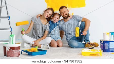 Repair In The Apartment. Happy Family Mother, Father  And Child Daughter    Paints The Wall With   P