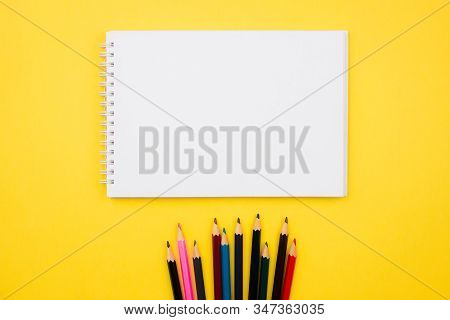 Sketchbook, Notebook And Color Pencils Flat Lay On Colorful Yellow Background. Top View With Copy Sp