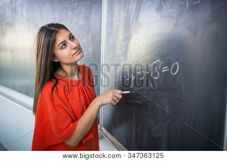 Pretty, young college student/young teacher writing on the chalkboard/blackboard during a math class