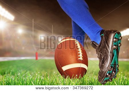 American Football Player Prepares To Kick Ball For Conversion Points Or Field Goal In Brightly Lit O