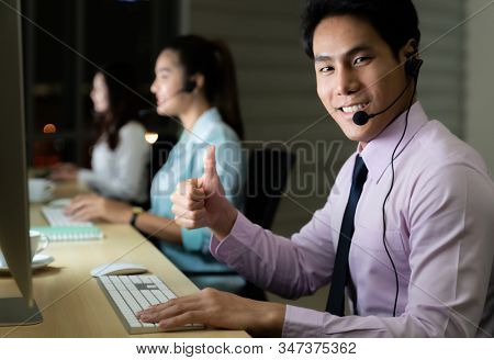 Asian young adult confidence operator man agent with headsets working in a call center at night Environment with his colleague team as customer service. Using as Late night Hard working 24 hours.