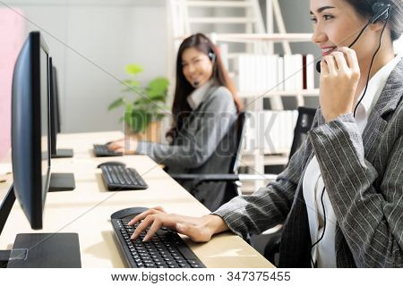 Young adult friendly and confidence operator woman agent smiling with headsets working in a call center with her colleague team working as customer service and technical support workplace background.