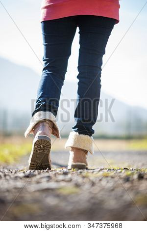 Low Angle View Of A Woman In Winter Boots Walking On Footpath.