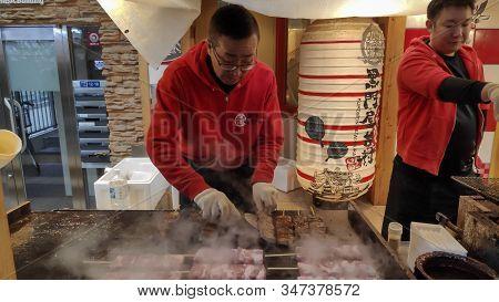Osaka, Japan- 28 Nov, 2019: Small Street Seafood Restaurant With Chef Cooking Yakitori On Stove For
