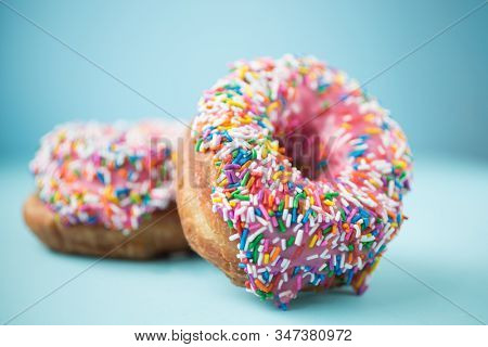 Two donuts with pink icing and candies on a blue pastel background