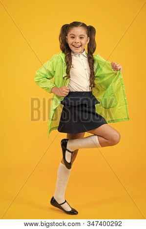 Ready To Walk In Any Weather. Energetic Schoolchild Smiling On Yellow Background. Little Girl Feelin