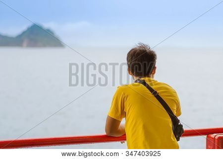 Asian Man Stands On Baluster Of Ferry For Relaxing And Look At The Ocean And Island.