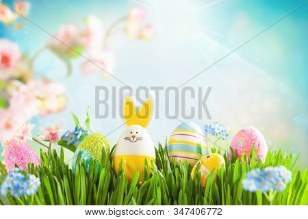 Easter eggs and spring flowers on meadow. Easter concept. Spring or summer background with fresh grass on blue sky backdrop with copy space.