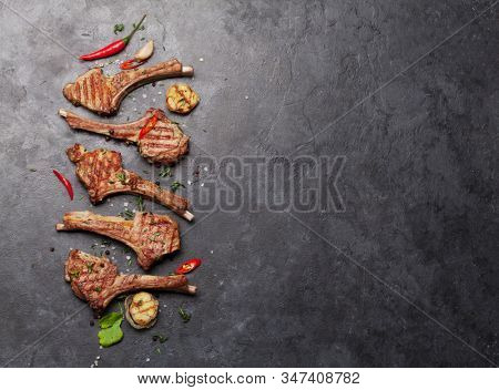 Grilled lamb ribs. Hot rack of lamb with spices and condiments. Top view on stone table with copy space
