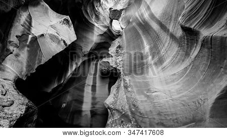 Black And White Photo Of The Smooth Curved Red Navajo Sandstone Walls Of The Upper Antelope Canyon,