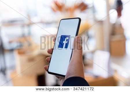Chiang Mai, Thailand - Jan.18,2020: Man Holding Xiaomi Mi Mix3 With Facebook App On The Screen.