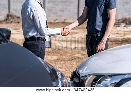 Insurance Agent And Customer Shaking Hands After Agreement About In Insurance Claim, Assessed Examin