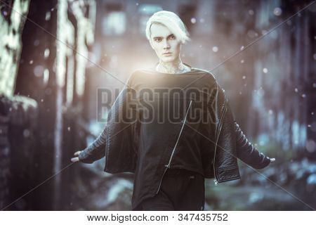 A magic portrait of a young fair-haired guy walking in the street. Casual fashion, beauty.