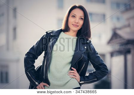Young fashion woman with handbag on city street Stylish female model in black leather jacket and light gray pullover