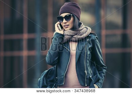 Young fashion woman in black leather jacket talking cell phone  Stylish female model in sunglasses beanie and snood scarf on city street
