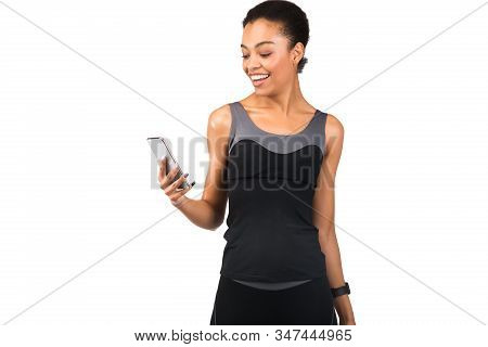 Sporty African American Girl In Fitwear Using Smartphone Standing On White Studio Background. Fitnes