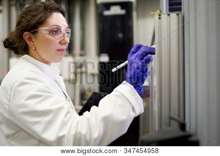 Lab assistant woman in white coat records results in laboratory