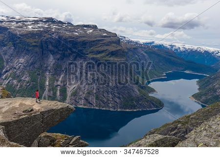 Woman Standing On Edge Of Cliff At Trolltunga Mountain In Norway.