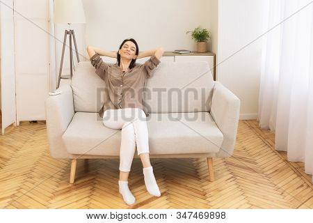 Weekend. Relaxed Calm Woman Resting At Home On Sofa, Satisfied Young Lady Stretching On Couch, Leani
