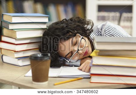 Sleeping At Library. Tired Mexican Girl Student Napping On Books Stack, Being Exhausted During Prepa