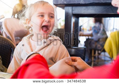 Beautiful toddler child girl sitting on baby highchair  crying front of a woman