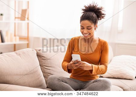 Happy African American Woman Using Mobile Phone And Wireless Earphones Making Video Call Sitting On