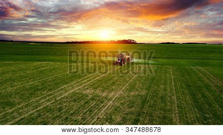 Farmer Working In The Field On A Tractor Until Sunset