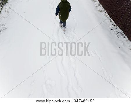 A Surveillance Camera  Like Image Of An  Unrecognizabl Woman Walking Away, Winter Scene