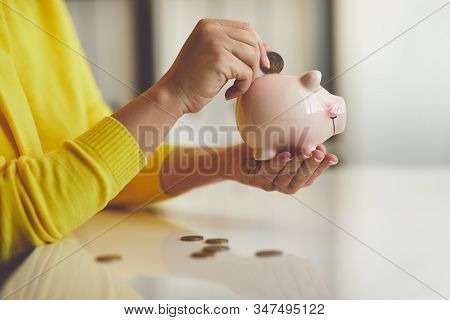 Woman Puts Euro Coin Into Piggy Bank