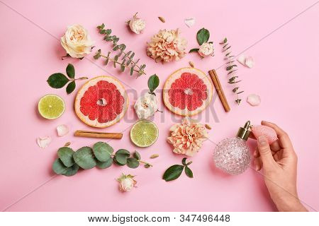 Top View Of Woman Spraying Perfume On Pink Background, Flowers And Citrus Fruits Representing Aroma
