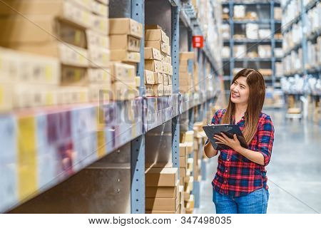 Asian Woman Warehouse Worker Standing And Checking Goods Stock In Warehouse And Writing In Clipboard