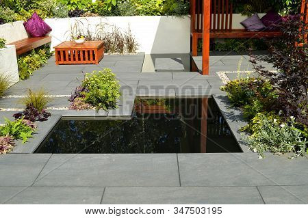 Low Maintenance Garden With A Stone Patio And Ornamental Garden Pond