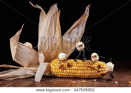 Corncob On A Wooden Table With Popcorn Figures On It, Black Background