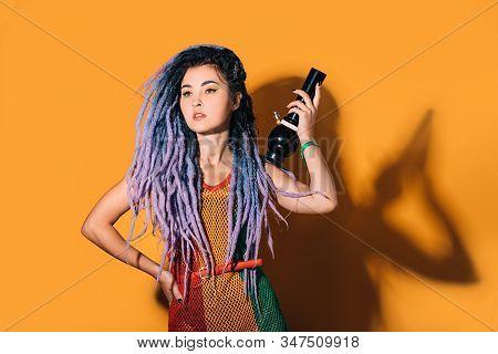 Rasta Woman Holds A Bong In Her Hand. Legalization Of Marijuana. Cannabis Smoking Bong