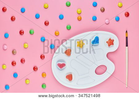 Art Of Sweetmeats Concept. Sweet Candy In Paint Palette On Pink Background. Love To Colorful Sweetme