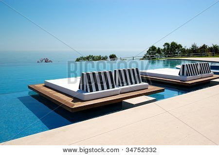 Infinity swimming pool by beach at the modern luxury hotel Pieria Greece poster