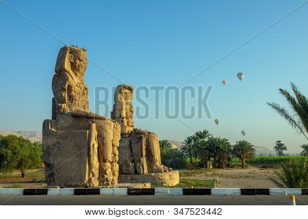 Colossi of Memnon gigantic statues and air balloons in Luxor Egypt