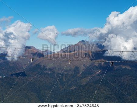 Suspension Bridge Hanging Over A Mountain Abyss Against The Backdrop Of Large White Clouds And Blue