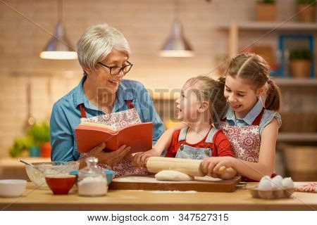 Happy loving family are preparing bakery together. Granny and children are cooking cookies and having fun in the kitchen. Homemade food and little helper.