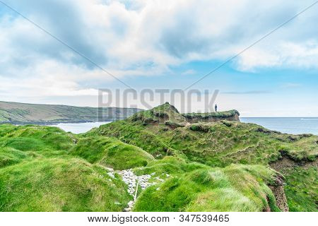 Man Standing On A Cliff And Looking At The Ocean On Hazy Spring Day. Southwest Of Ireland.