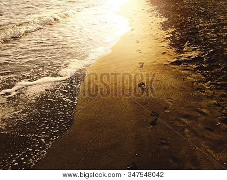 Human Footprints On The Sand Of A Beach On The Shore With Foamy Waves And The Light Of The Setting S