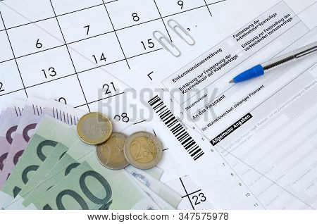 German Tax Form With Pen And European Money Bills Lies On Office Calendar. Taxpayers In Germany Usin