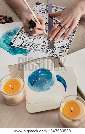 Selective Focus Of Fortuneteller Drawing Birth Chart By Cards With Watercolor Paintings And Candles