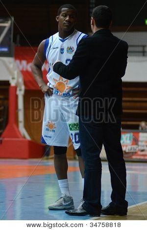 KAPOSVAR, HUNGARY - FEBRUARY 22: Kwadzo Ahelgebe listening to trainer at a Hungarian Cup basketball game with Kaposvar (white) vs. Fehervar (blue) on February 22, 2012 in Kaposvar, Hungary.