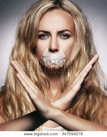 Woman with mouth sealed plaster. Fear, silence and violence