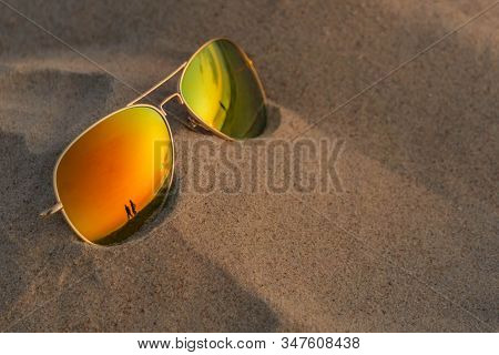 Mirrored Sunglasses Close Up On Beach Sand With Sundown And Couple Reflection. Reflecting Sunglasses