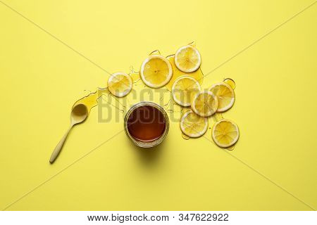 Honey Jar And Lemon Slices With Honey On Them, On Yellow Background. Flat Lay Of Lemons And Honey. N