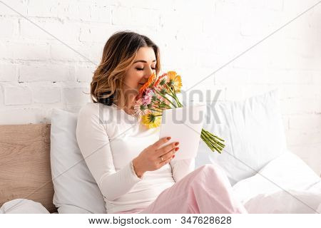 Happy Woman Holding Bouquet Of Gerberas And Mothers Day Card While Sitting In Bed