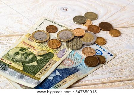 Bulgarian Lev Banknotes And Coins On A White Wooden Surface. Bulgarian Paper And Metal Money On A Ta